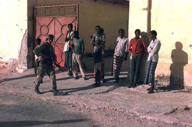 Shot of a US Marine from Battalion Landing Team 29, 1ST Marine Expeditionary Force, Camp Pendleton, California, walking cautiously and carrying a M16 rifle through a civilian sector of Mogadishu, as there are reports that snipers are still in the area. Local residents gather as curious on-lookers. This mission is in direct support of Operation Restore Hope