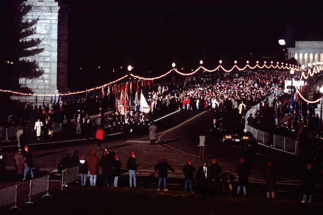 """American Reunion on the Mall. The U. S. Honor guard escorts President-elect Clinton as he walks over memorial bridge to Lady Bird Johnson Park for the symbolic """"Ringing of the Bells"""". The ceremony was the last before a large crowd gathered on the national mall for the """"American Reunion"""""""