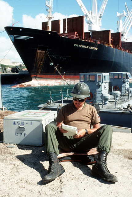 Signalman 3rd Class Rick Maddox, a member of Amphibious Construction Battalion 1 (ACB-1), reads from a pad while sitting in front of the maritime prepositioning ship PVT. FRANKLIN J. PHILLIPS (T-AK-3004) during the multinational relief effort Operation Restore Hope