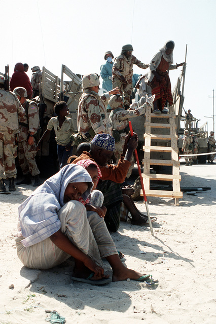 Two Somali girls look into the camera as a woman is assisted off a truck after being examined by a navy corpsman as part of a medical civic action program during the multinational relief effort Operation Restore Hope