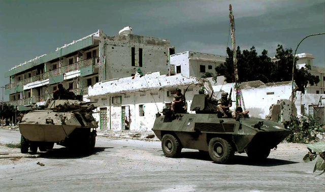 "A US Marine Cadillac Gage Light Armored Reconnaissance Vehicle from the 3rd Light Armor Infantry Battalion (left) and Italian Soldiers in a Fiat-OTO Melara Type 6614 Armored Personnel Carrier (right) guard an intersection on the ""Green Line"" in Mogadishu. The line divides the northern and southern part of the city and warring clans. This mission is in direct support of Operation Restore Hope"