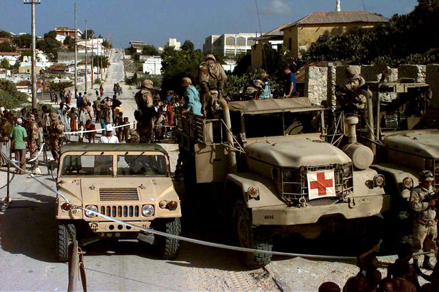 A US Marine M998 High-Mobility Multipurpose Wheeled Vehicle (HMMWV) and two M54 Series 5-ton Cargo Trucks. The vehicles are parked on a Mogadishu street and are cordoned off with white tapes. Several locals have gathered around the circumference of the tape. This are has become a walk-in medical and dental clinic for the residents of the capital city. Medical personnel from the Expeditionary Unit, Service Support Group 15, Camp Pendleton, California conducted medical civic action program. This mission is in direct support of Operation Restore Hope