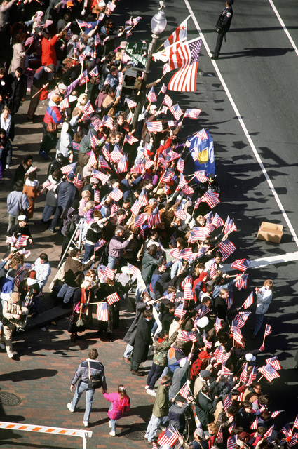 Parade viewers near the National Gallery of Art wave their US flags in anticipation of the passing of President Clinton during the 1993 Inaugural parade