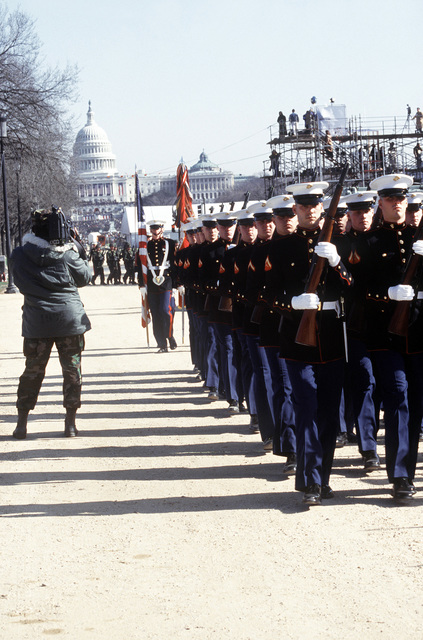 SGT Newton Buchner (USAF) videographer, videotapes the US Marine Corps Company practicing on the Mall before marching down the parade route