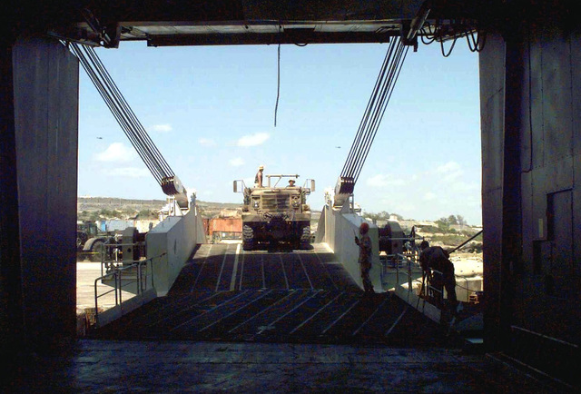 View from inside and out of the back of the Military Sealift Command Ship Private Franklin W. Phillips. A US Marine M54 Series 5-ton Cargo Truck comes up the stern ramp for back loading in the Port of Mogadishu, Somalia. The maritime prepositioning ship began back loading military vehicles and equipment used during the early stages of Operation Restore Hope by Joint Task Force Somalia