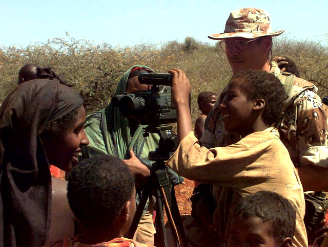 US Navy CHIEF Photographer's Mate Robert Sasek allows a Somali boy from the village of Maleel to look through the viewfinder of his video camera. Sasek, an Alton, Illinois native, is deployed with Pacific Fleet Combat Camera Group to Somalia to document the efforts of Joint Task Force Somalia. Sasek was outside the village to document the delivery of wheat to the villagers by US Marine helicopters (not shown). This mission is in direct support of Operation Restore Hope