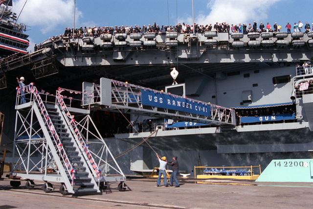 Crew members gather at the railings of the aircraft carrier USS RANGER (CV-61) as the gangplank is lowered following the vessel's return from deployment in the Persian Gulf during OPERATION SOUTHERN WATCH AND RESTORE HOPE. The Persian Gulf deployment represents the RANGER's final mission prior to decommissioning