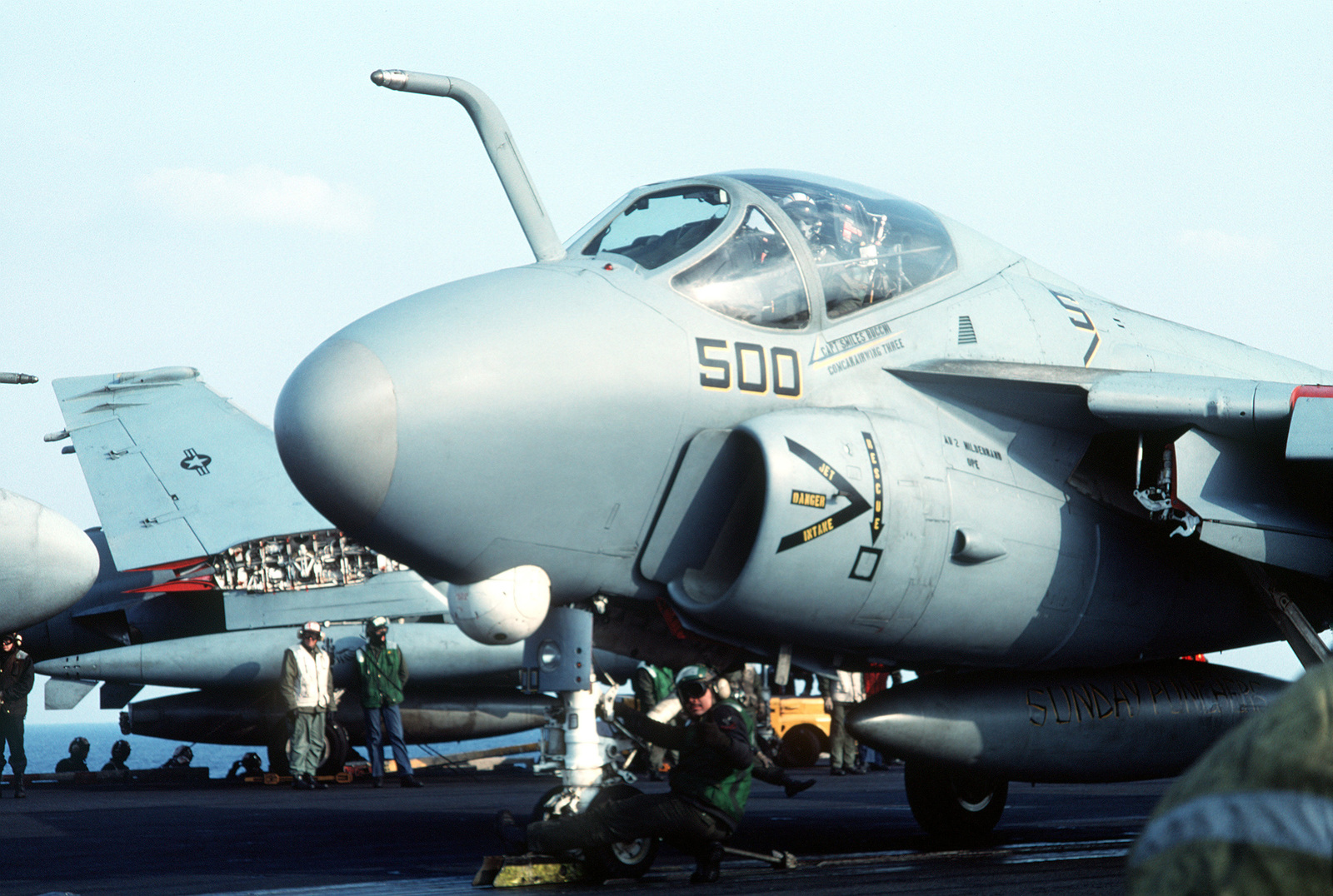A member of the holdback/hookup crew signals to the catapult officer as the catapult crew prepares to launch an Attack Squadron 75 (VA-75) A-6E Intruder aircraft from the aircraft carrier USS JOHN F. KENNEDY (CV-67)