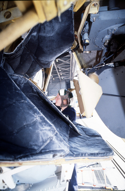 Aviation Machinist's Mate AIRMAN (ADAN) Rita Weldon works inside the nose cone of a P-3C Orion aircraft. ADAN Weldon is attached to Patrol Squadron Twenty Six (VF-26)