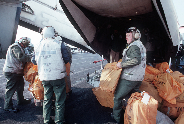 Flight deck personnel unload bags of mail from a Fleet Logistic Support Squadron 40 (VRC-40) C-2A Greyhound aircraft on the aircraft carrier USS JOHN F. KENNEDY (CV-67)