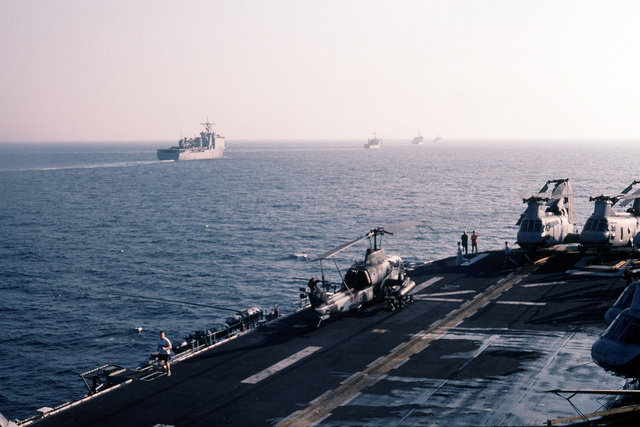 Marines run on the flight deck of the amphibious assault ship USS GUAM (LPH-9). The GUAM is sailing in formation with other ships of the aircraft carrier USS JOHN F. KENNEDY (CV-67) task force. An AH-1W Sea Cobra is one of the Marine Medium Helicopter Squadron 261 (HMM-261) helicopters staged on the flight deck of the GUAM