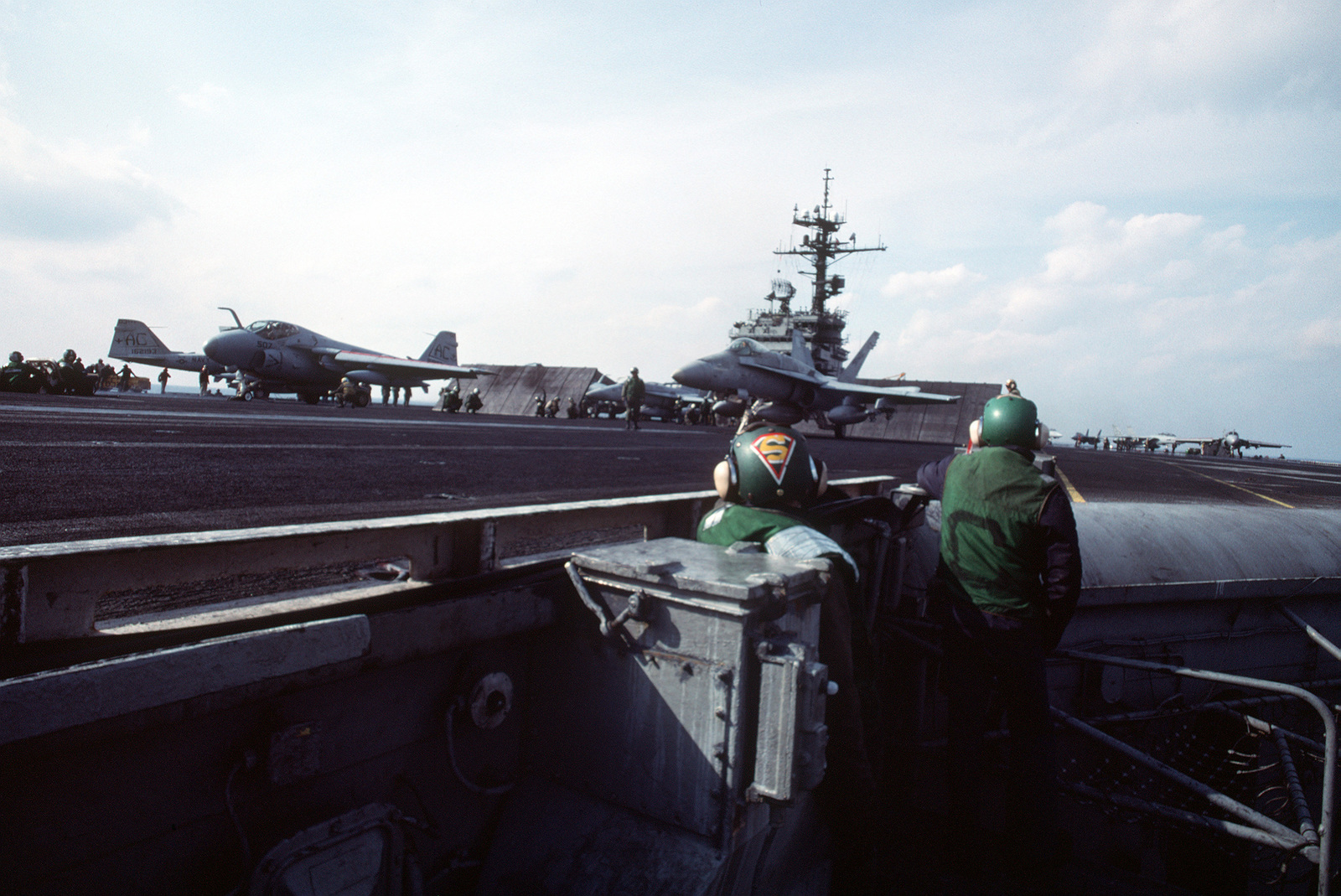Members of the catapult crew watch from the deck edge operator's station as an A-6E Intruder and an F/A-18C Hornet aircraft are prepared to be launched from the aircraft carrier USS JOHN F. KENNEDY (CV-67)