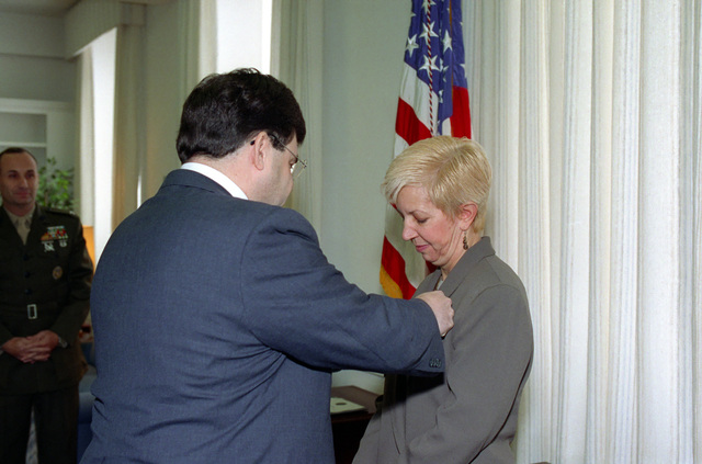 The Honorable James R. Locher, III (left), Assistant Secretary of Defense for Special Operations and Low Intensity Conflict, presents the Secretary of Defense Medal for Meritorious Civilian Service to Mrs. Janice S. Ervin (right), at an official ceremony in the Pentagon on Feb. 1, 1993.  OSD Package No. A07D-00119 (DOD PHOTO by Helene C. Stikkel) (Released)