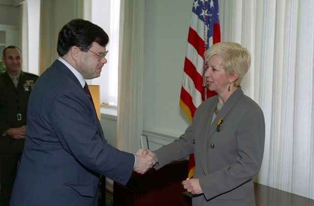 The Honorable James R. Locher, III (left), Assistant Secretary of Defense for Special Operations and Low Intensity Conflict, shakes hands with Mrs. Janice S. Ervin (right), after he presented her with the Secretary of Defense Medal for Meritorious Civilian Service at an official ceremony in the Pentagon on Feb. 1, 1993.  OSD Package No. A07D-00119 (DOD PHOTO by Helene C. Stikkel) (Released)