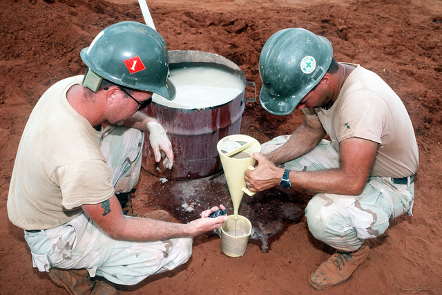While working on a water well drilling project, members of Naval Mobile Construction Battalion 1 (NMCB-1) time how fast a sample empties from a funnel to determine its viscosity. The well, near Bale Dogle, is intended to supply an old Soviet air base being used by U.S. and Moroccan personnel participating in the operation