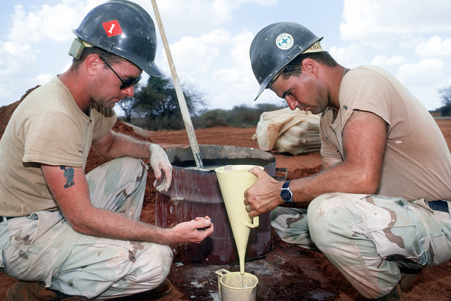 While working on a water well drilling project, members of Naval Mobile Construction Battalion 1 (NMCB-1) time how fast a sample empties from a funnel to determine the viscosity of the sample. The well, near Bale Dogle, is intended to supply an old Soviet air base being used by U.S. and Moroccan personnel participating in the operation