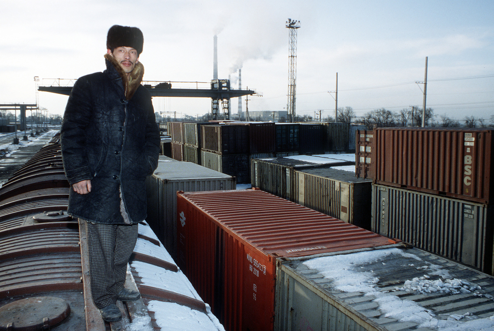 A local resident stands atop a railcar at the Kizghiz Railyard