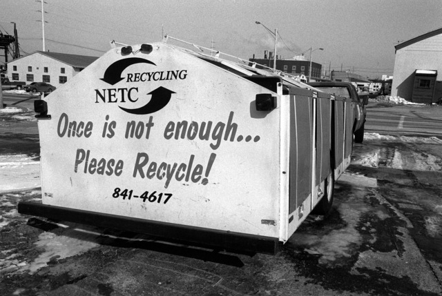 The motto of the Naval Education and Training Center (NETC) is painted on the side of a container for recyclables