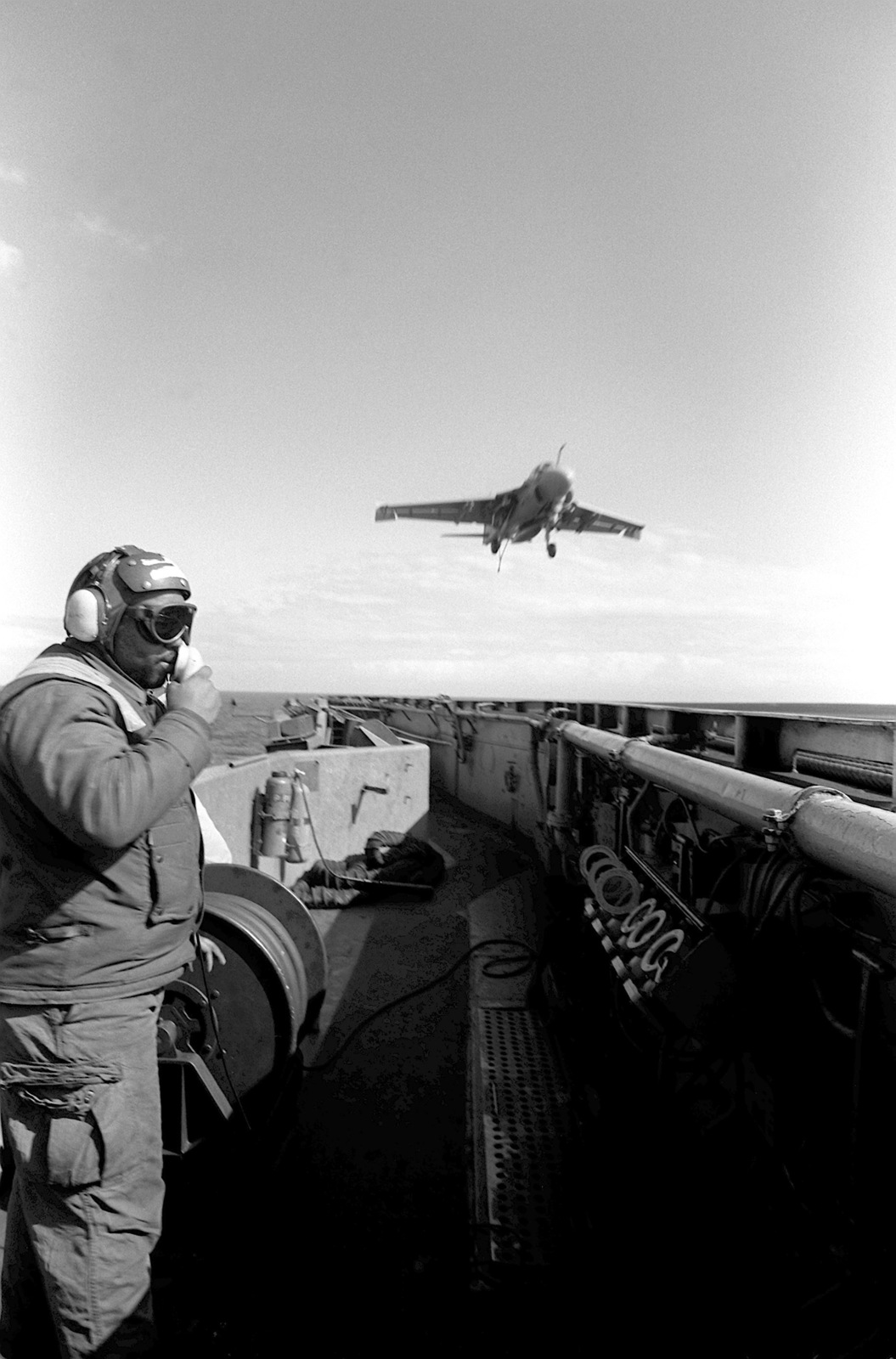 A flight deck crew member watches as an Attack Squadron 75 (VA-75) A-6E Intruder aircraft prepares to touch down on the flight deck of the aircraft carrier USS JOHN F. KENNEDY (CV-67) during flight operations aboard the vessel