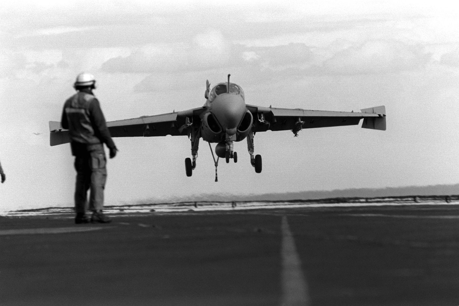 A flight deck crewman watches as an Attack Squadron 75 (VA-75) A-6E Intruder aircraft lands on the aircraft carrier USS JOHN F. KENNEDY (CV-67)