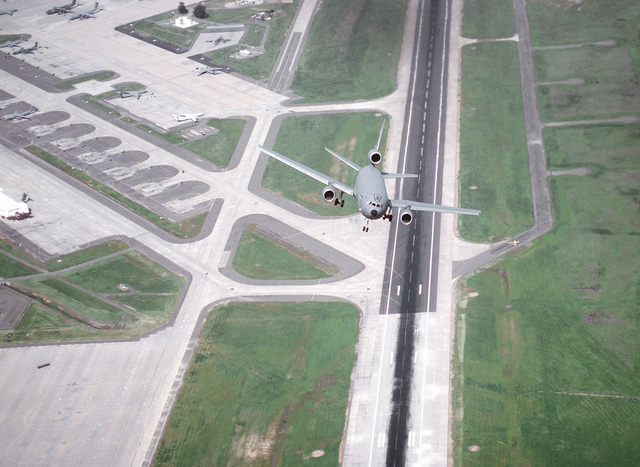 A 22nd Air Refueling Wing, March AFB, California, KC-10A Extender is seen from above as it takes off from 21R runway. The Travis flightline with C-141B Starlifters and C-5 Galaxys from the 60th Airlift Wing are in the background. Exact Date Shot Unknown
