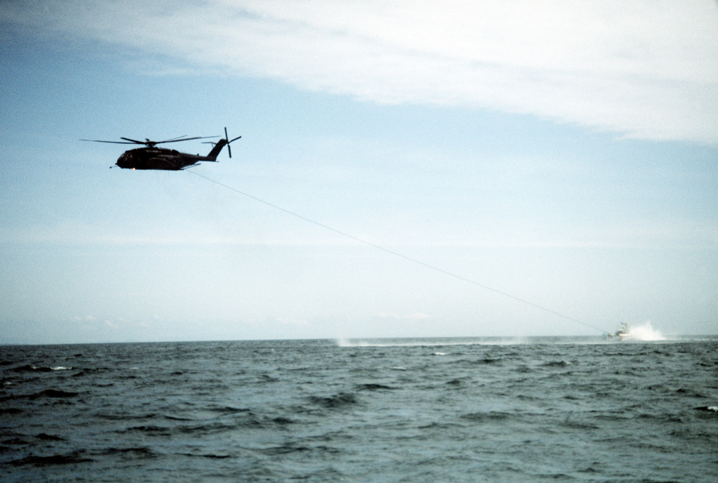 A Helicopter Mine Countermeasures Squadron 15 (HM-15) MH-53E Sea Dragon helicopter tows a Mark 105 hydrofoil minesweeping sled during the joint U.S.-Canadian fleet exercise MARCOT '93