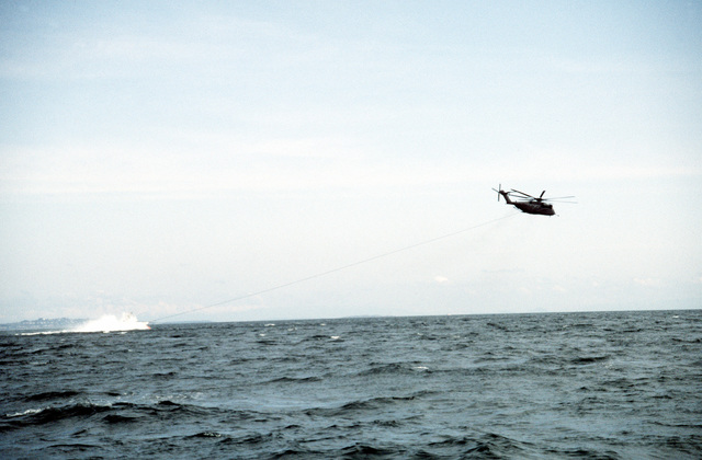 A Helicopter Mine Countermeasures Squadron 15 (HM-15) MH-53E Sea Dragon helicopter tows a Mark 105 hydrofoil minesweeping sled during the joint U.S. Canadian fleet exercise MARCOT '93