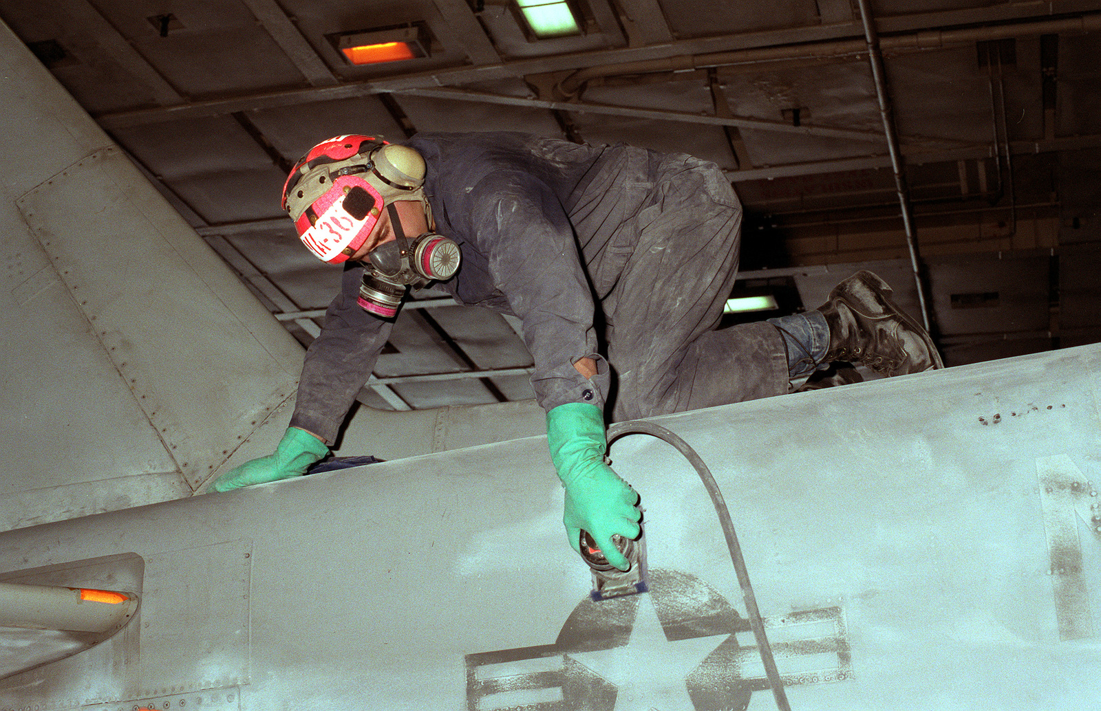 A member of Attack Squadron 36 (VA-36) sands part of the fuselage of an A-6E Intruder aircraft on the nuclear-powered aircraft carrier USS THEODORE ROOSEVELT (CVN-71) during Operation Deny Flight