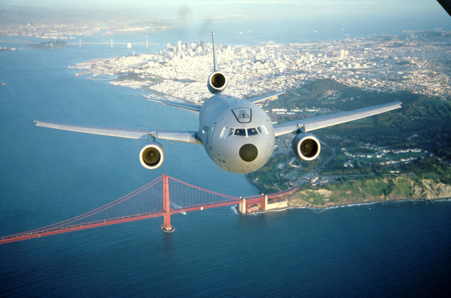 Air-to-air, front view of a 22nd Air Refueling Wing KC-10A Extender from March AFB, California flying over the Golden Gate Bridge with the city of San Francisco and the Bay Bridge in the background. Exact Date Shot Unknown
