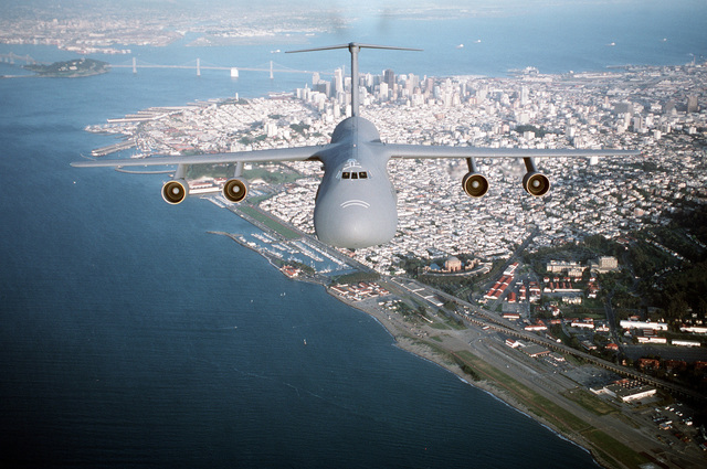 Air-to-air, front view of a 60th Airlift Wing C-5B Galaxy airlifter, flying over San Francisco Bay with San Francisco and the Bay Bridge in the background.Exact Date Shot Unknown