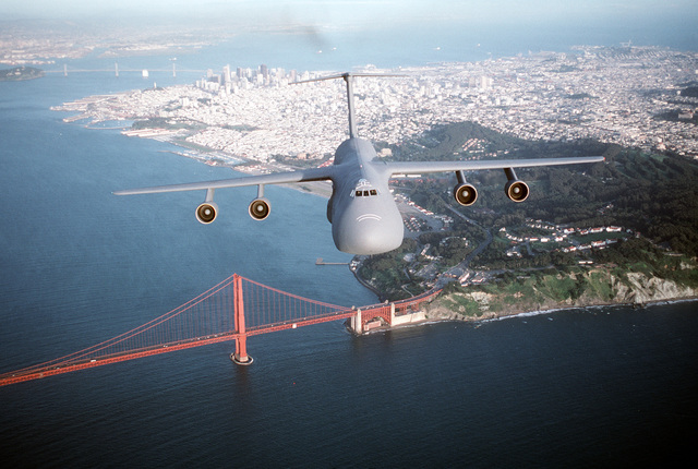 Air-to-air, front view of a 60th Airlift Wing C-5B Galaxy airlifter, flying over the Golden Gate Bridge with Presidio, San Francisco and the Bay Bridge in the background. Exact Date Shot Unknown