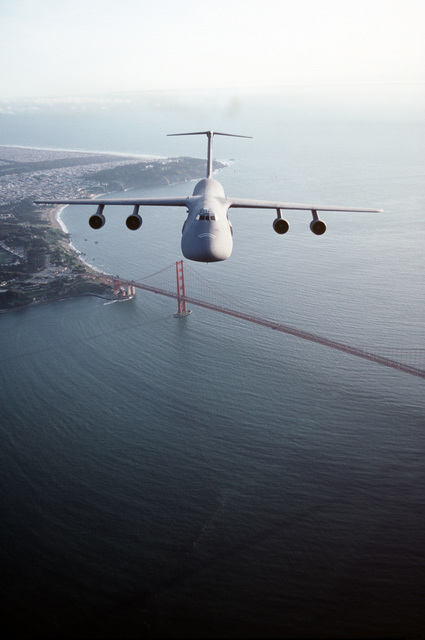 Air-to-air, front view of a 60th Airlift Wing C-5B Galaxy airlifter, flying over the Golden Gate Bridge with Presidio and ocean in the background. Exact Date Shot Unknown