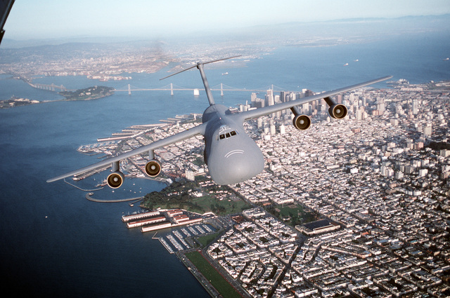 Air-to-air, front view of a 60th Airlift Wing C-5B Galaxy airlifter, flying over San Francisco Bay with San Francisco and the Bay Bridge in the background. Exact Date Shot Unknown