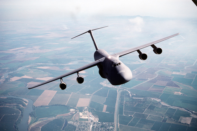 Air-to-air, front view of a 60th Airlift Wing C-5B Galaxy airlifter, with left wing high, flying over the farmland of northern California. Exact Date Shot Unknown