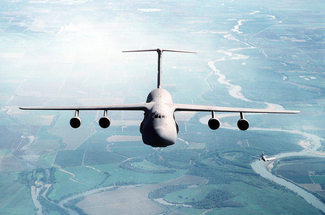 Air-to-air, high, front view of a 60th Airlift Wing C-5B Galaxy airlifter, flying over the farmland of northern California. An inflight KC-10 Extender is seen in the lower right. Exact Date Shot Unknown