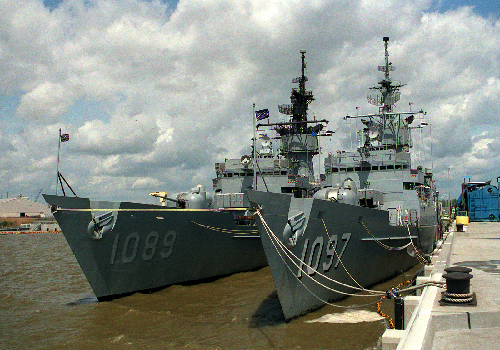 The frigate USS MOINESTER (FF-1097) and USS JESSE L. BROWN (FF-1089) are moored together at a pier at a Mobile shipyard