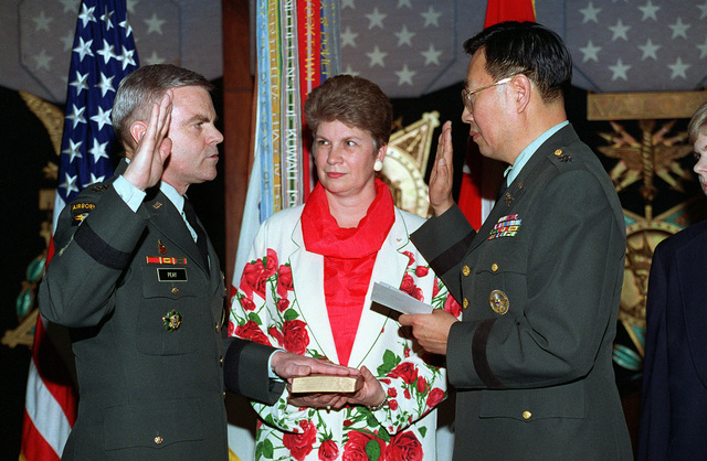 The Judge Advocate of the United States Army, Major General John L. Fugh administers the oath of office to the Vice CHIEF of STAFF, General J.H. Binford Peay. General Peay's wife Pamela holds the Bible