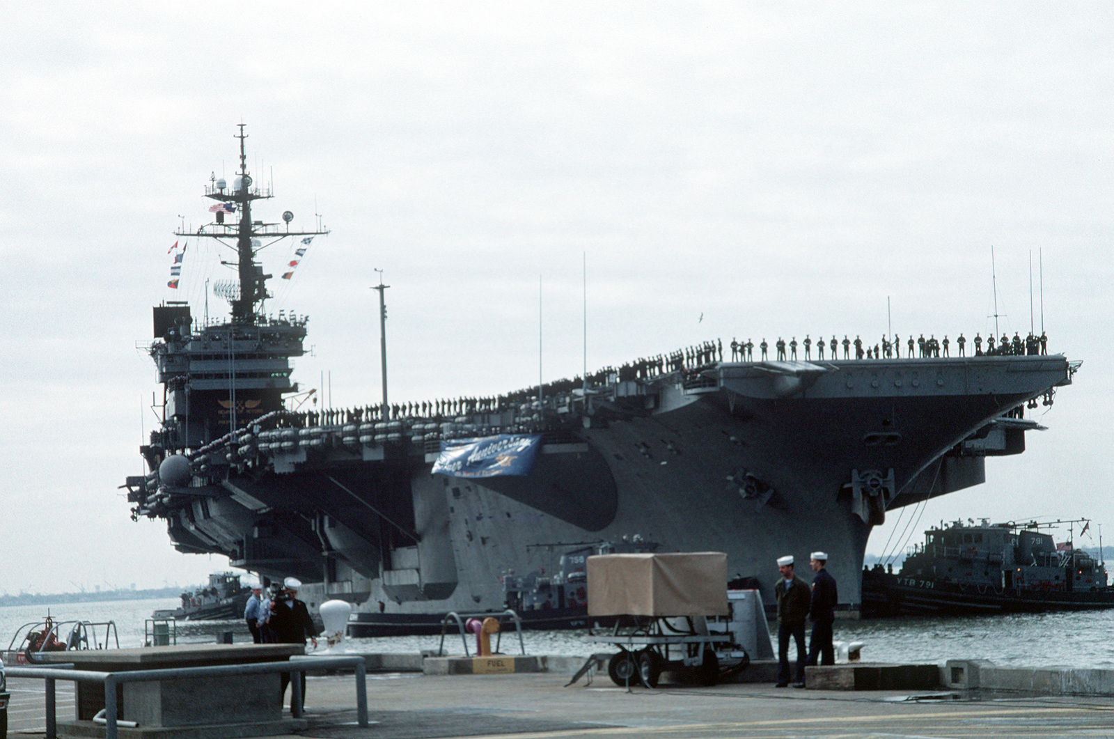 crewmen man the rails as the aircraft carrier uss john f kennedy