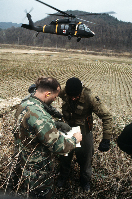 Army SPC John R. Olney, a UHF-60 Black Hawk (Blackhawk) Helicopter crew chief, looks over a terrain map with CAPT. Robert Mitchell. Both are assigned to 377th Medical Company, K-16, Seoul AB, Korea. They were inserted into a remote area as part of a Combat Search and Rescue training mission and are preparing to begin the escape/evasion portion of the exercise