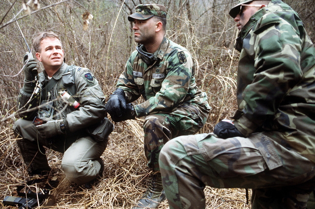 CAPT. John Cottrell, a helicopter pilot from the 38th Air Rescue squadron (ARS), establishes radio contact with Forward Air Control aircraft (OA-10) while CAPT. Robert Mitchell and SPECIALIST John Olney look on. The group was part of a joint training exercise held in the mountains of South Korea