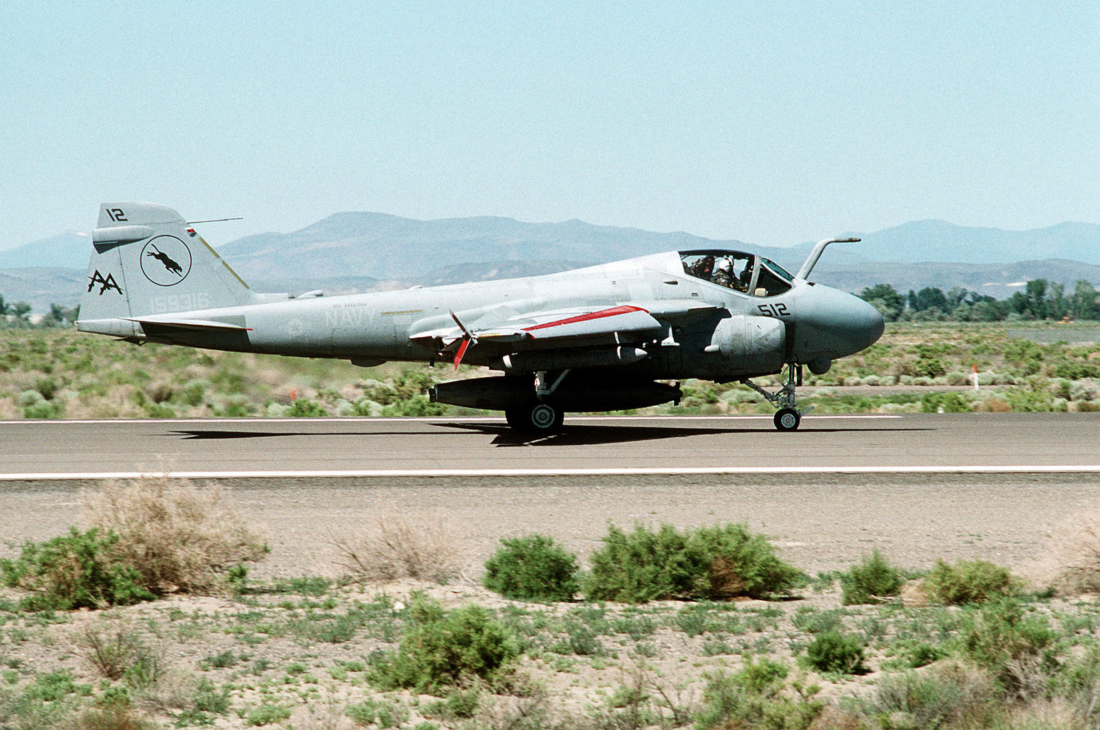 An Attack Squadron 65 (VA-65 ) A-6E Intruder aircraft taxis on the runway after landing following a training sortie with Carrier Air Wing 17 (CVW-17) against a simulated radar threat environment. The aircraft is equipped with a fuel storage tank for aerial refueling missions