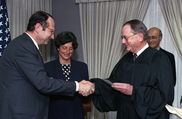 An unidentified Justice congratulates John M. Deutch (left), newly appointed Under Secretary of Defense for Acquisition, at his Oath of Office Ceremony at the Pentagon, Washington, D.C., on April 15, 1993.  His wife, Patricia Lynn Deutch, is present.  OSD Package No. A07D-00180 (DOD PHOTO by Robert D. Ward) (Released)