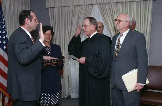 The Honorable Leslie 'Les' Aspin (right), U.S. Secretary of Defense, hosts the Oath of Office Ceremony of John M. Deutch (left), newly appointed Under Secretary of Defense for Acquisition, at the Pentagon, Washington, D.C., on April 15, 1993.  Patricia Lynn Deutch is holding the bible upon which her husband has his left hand resting.  OSD Package No. A07D-00180 (DOD PHOTO by Robert D. Ward) (Released)