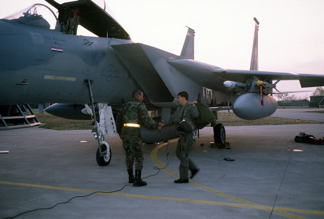 The pilot of a 53rd Fighter Squadron F-15C Eagle is greeted by his crew chief as he arrives to make a preflight check of his aircraft before a mission during Operation Deny Flight, the enforcement of the United Nations-sanctioned no-fly zone over Bosnia and Herzegovina