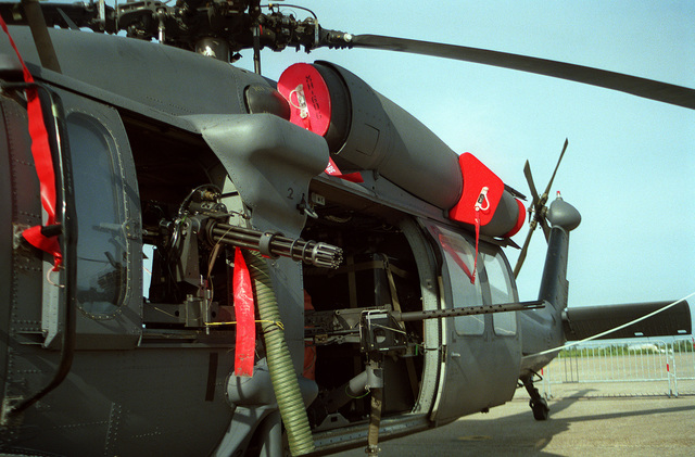 A close-up left side view of an Air Force MH-60G Pave Hawk helicopter on display during an air show. This helicopter is armed with one 7.62mm GAU-2/A mini-gun and one .50-caliber M-2 machine gun on each side