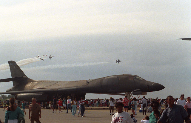 A right side view of a B-1B Lancer aircraft on display during an air show. In the background the Thunderbirds flight demonstration team performs an aerial maneuver for the crowd