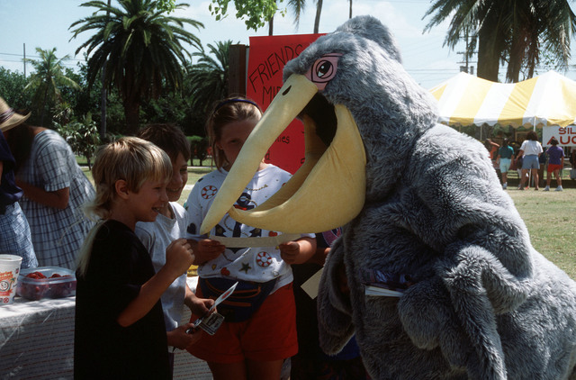 "Boatswain's Mate 2nd Class Amado Palermo, wearing the Navy Recycling Center's ""Pelican Pete"" mascot suit, hands out bumper stickers to children during Earth Day activities at Balboa Park. Palermo is from Naval Air Station, Key West"