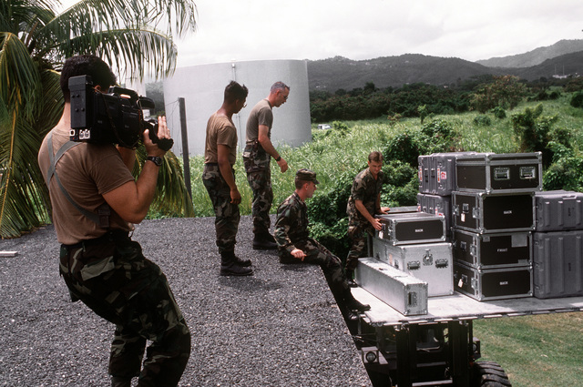 A cameraman shoots video footage of members of the Joint Combat Camera Satellite Team as they prepare to move boxes of satellite transmitter parts to the roof of the Fleet Imaging Command photo lab. The transmitter will be used to send video footage of the joint service exercise Ocean Venture '93 to the Joint Combat Camera Center at the Pentagon