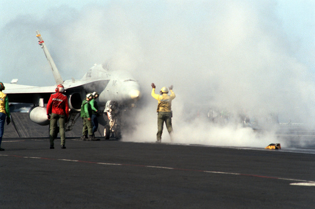 A flight deck crewman directs an F/A-18C Hornet aircraft of Marine Fighter Attack Squadron 312 (VMFA-312) onto a catapult aboard the nuclear-powered aircraft carrier USS THEODORE ROOSEVELT (CVN-71) during Operation Deny Flight