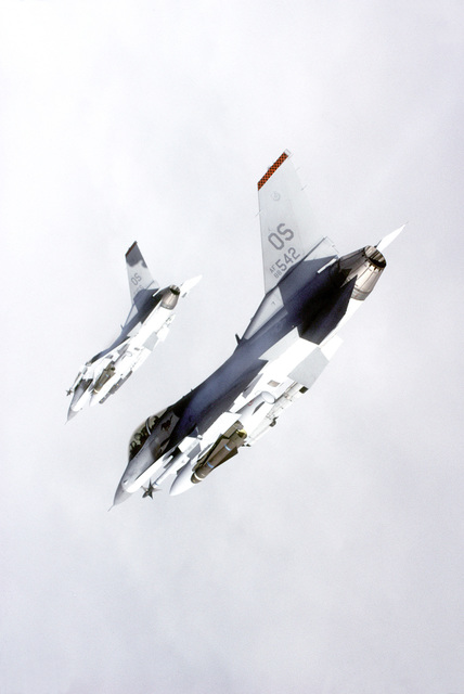 An air-to-air underside view of two F-16 Fighting Falcons from the 51st Fighter Wing flying in tight formation. The aircraft are armed with AGM-65 Maverick air-to-surface missiles and AIM-9 Sidewinder air-to-air missiles